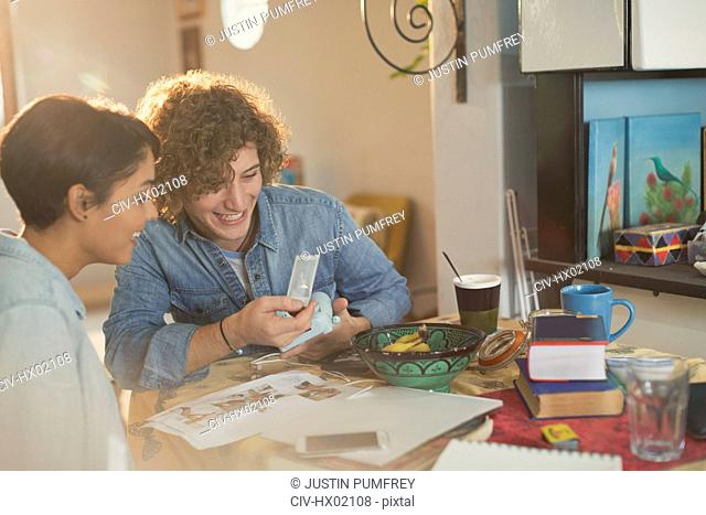 Young couple looking at instant photographs at table