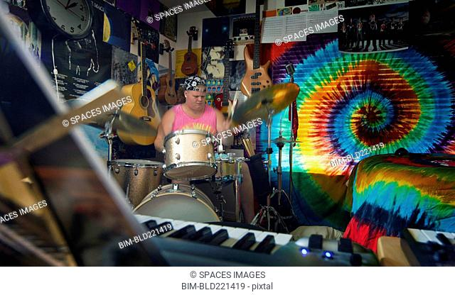 Caucasian man playing drums in music studio