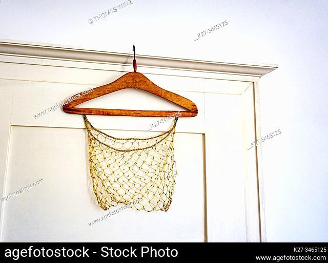 Old wooden coat hanger on a door ledge