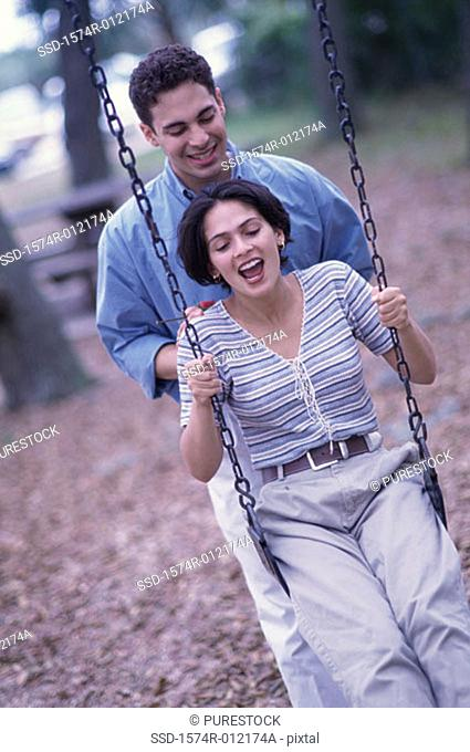 Young man pushing a young woman on a swing