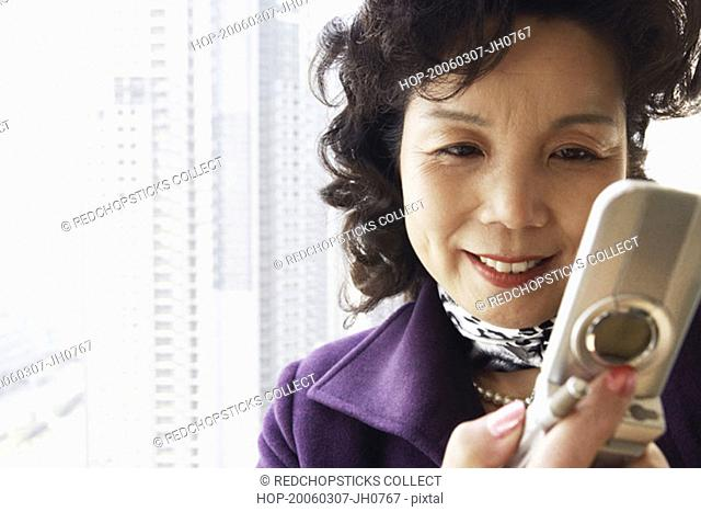 Close-up of a businesswoman operating a mobile phone smiling