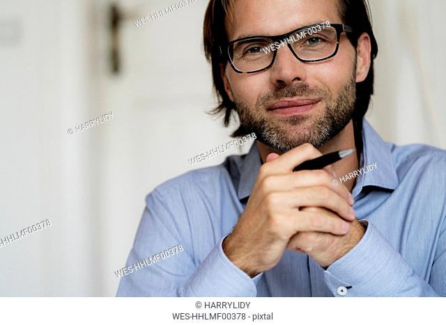 Portrait of confident man wearing glasses and holding pen