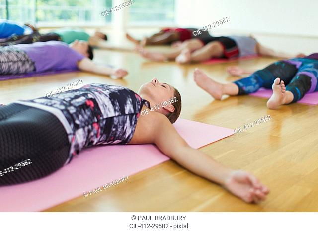 Serene woman in corpse pose in yoga class