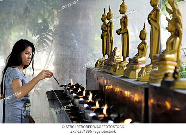 Woman praying in Wat Patum Wanaram Tample. Bangkok. Wat Pathum Wanaram is a Buddhist temple in Bangkok, Thailand. It is located in the district Pathum Wan