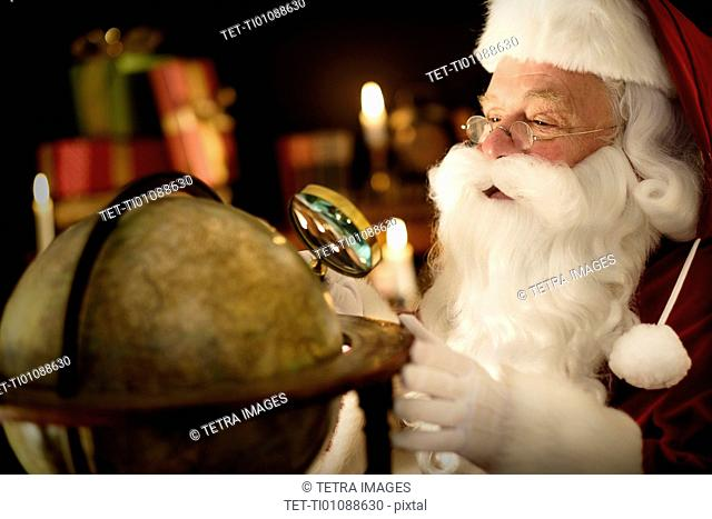 Santa Claus looking through magnifying glass at globe