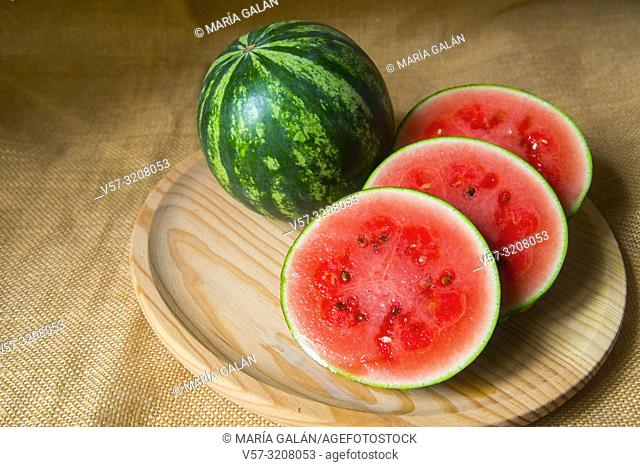 Two watermelons, one of them cut in slices. Still life