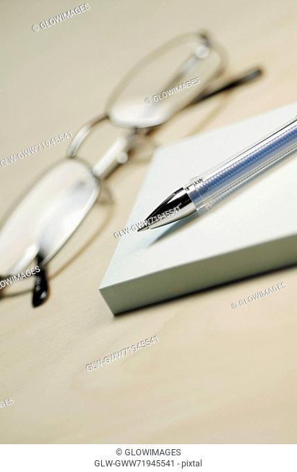 Close-up of a pair of eyeglasses with a pen and adhesive notes