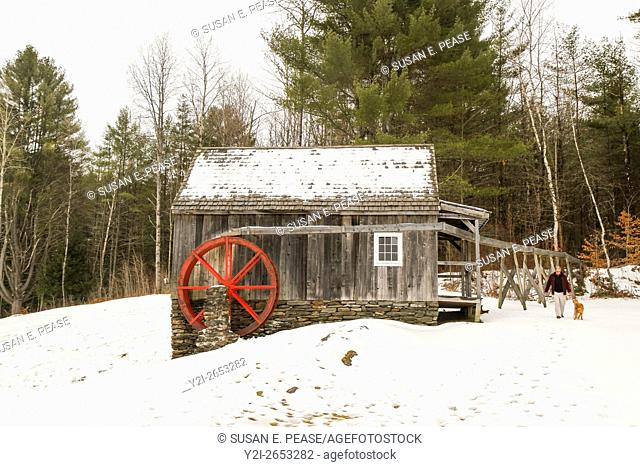 A man walks a dog near a building on the hillside near the Vermont Country Store, Rockingham, Vermont, United States, North America