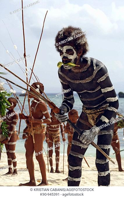 Melanesian man seen from front painted with coal to look like a sea snake performing the traditional Snake Dance with other dancers in the background at the...