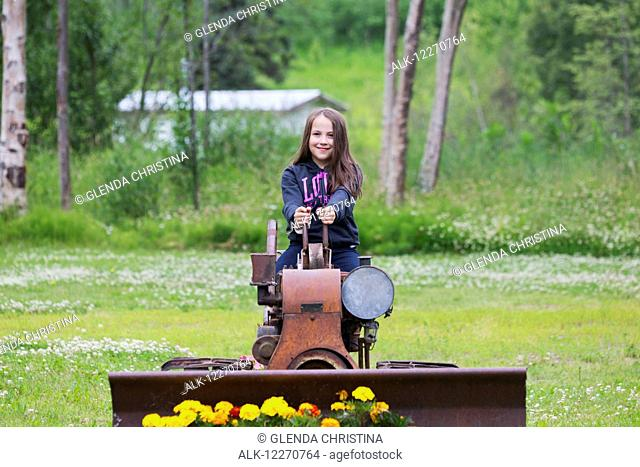 Tween Inupiat Eskimo girl sitting on an old tractor at the Knik Goose Bay Museum in Wasilla, Southcentral Alaska