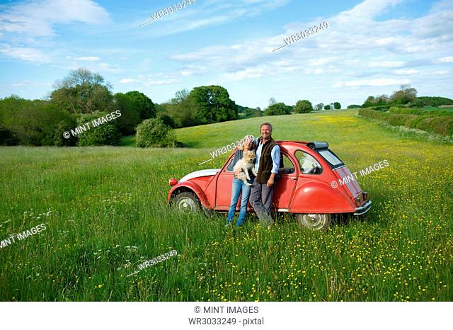 Man and woman standing side by side on a meadow, holding small dog, leaning against red vintage car