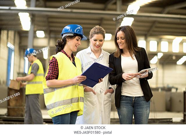 Female boss listening to her coworkers in factory