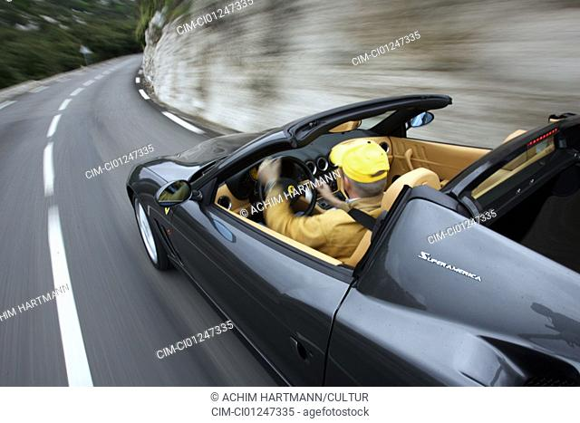 Car, Ferrari Superameriapprox. model year 2005-, black, Convertible, coupe/Coupe, driving, diagonal from the back, side view, panned shot , verwischt, open top