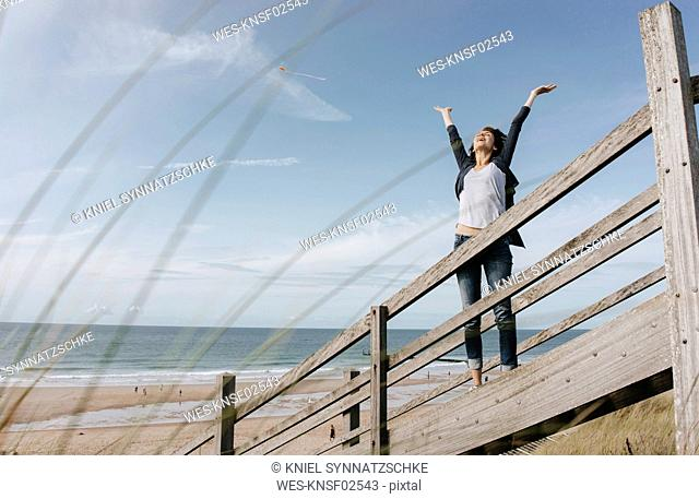 Happy woman standing on boardwalk at the beach with raised arms