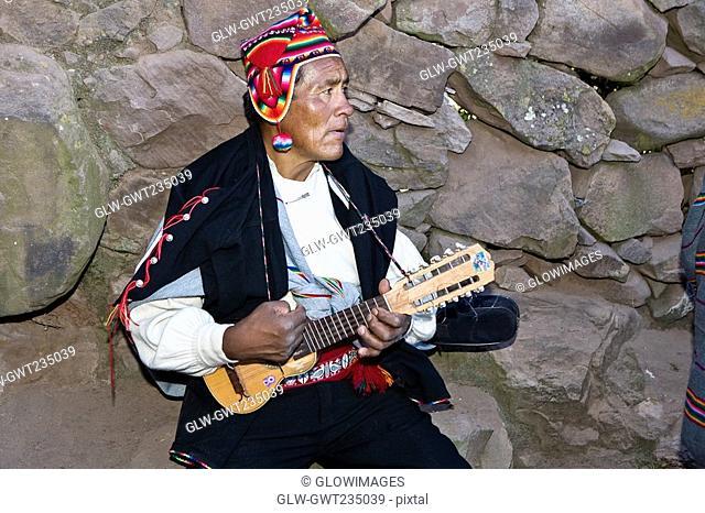 Close-up of a senior man playing a ukulele, Taquile Island, Lake Titicaca, Puno, Peru