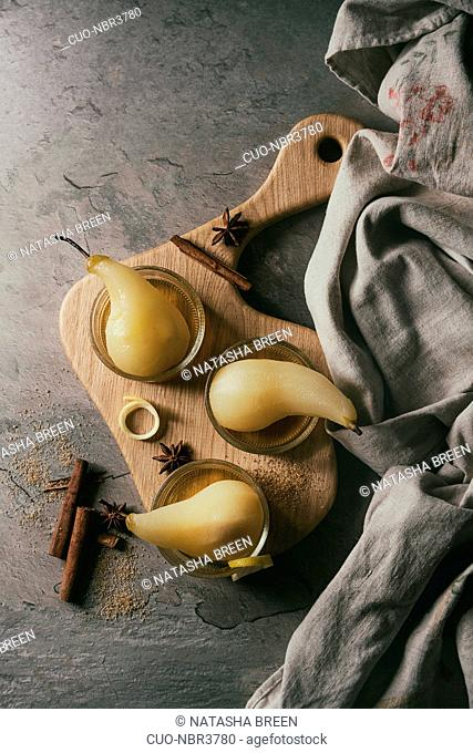Traditional dessert poached pears in white wine served in glass bowls with syrup and lemon zest on wooden serving board over gray texture table