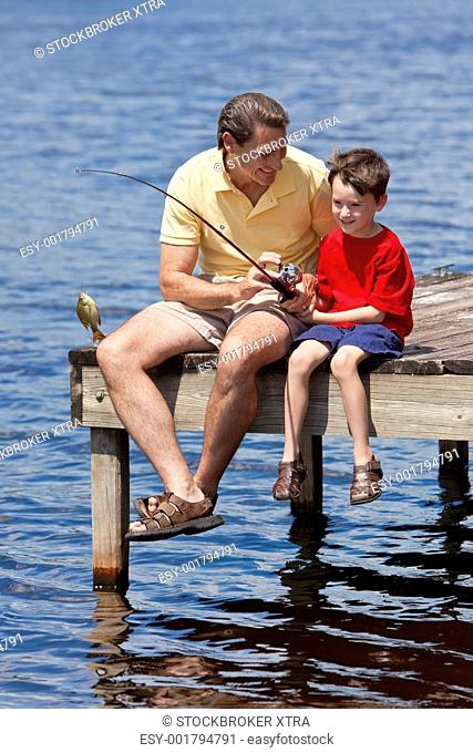 A father teaching his son fishing and catching a fish on a jetty outside in summer sunshine