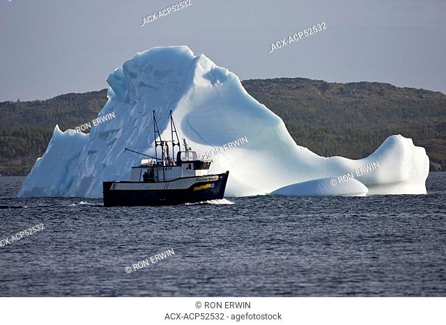 A fishing boat passes by a medium-sized iceberg near the shore of the town of St. Lunaire-Griquet on the island of Newfoundland, Newfoundland and Labrador