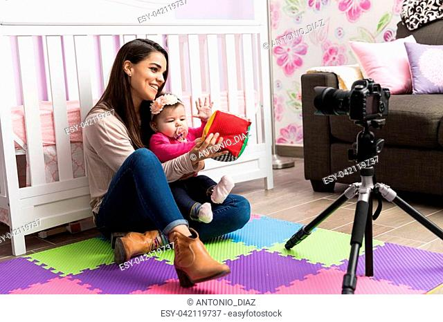 Cute young parenting blogger recording a video with her baby at home