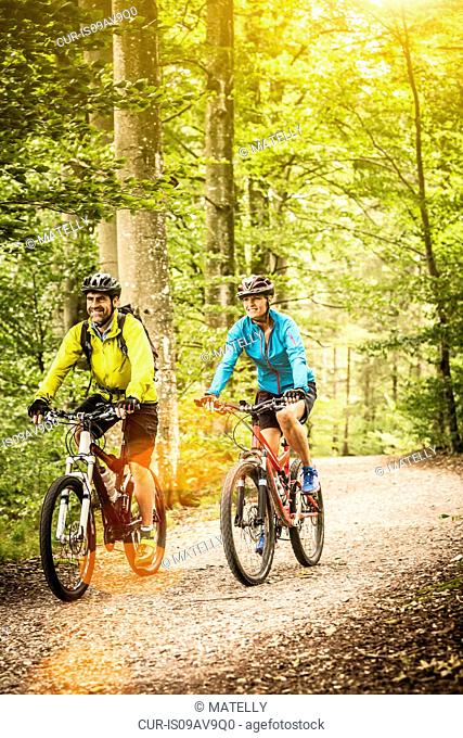 Happy mature mountain biking couple cycling on forest trail