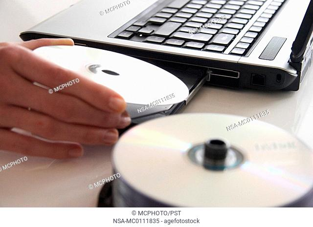 a hand, a laptop and some discs
