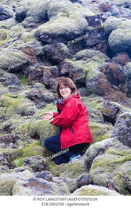 Female tourist amazed at the thickness of moss growing on the Eldhraun Lava Field in Iceland