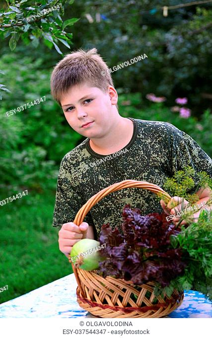 Teen Boy with a basket of fresh vegetables in the garden