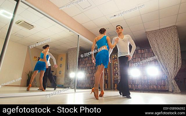 Young beautiful man and woman dancing and practicing Latin dance in costumes in the Studio, sports and leisure concept