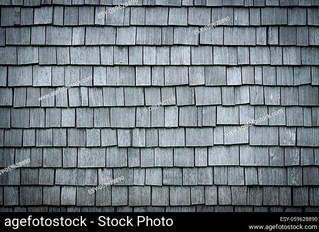 Old weathered Shingles wooden wall background. Traditional shakes with nice grey texture with nice vignetting spotlight. Bavaria, Allgau, Germany