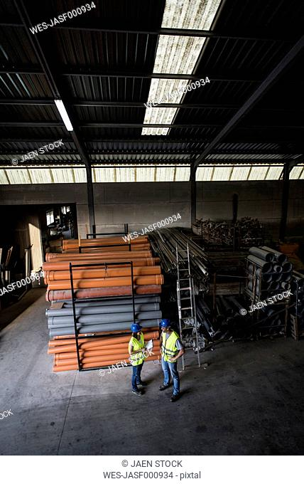 Man and woman working in warehouse of construction company