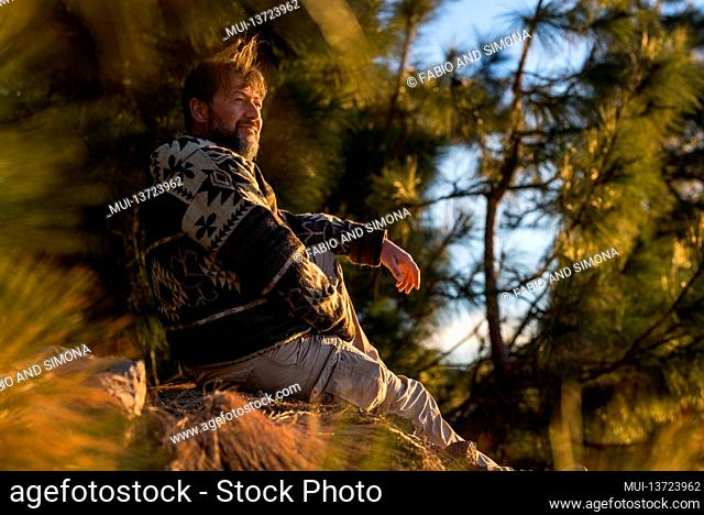 Handsome man sit down on the ground nature smile and enjoy the outdoor lifestyle - trees and forest woods in background - concept of travel and relaxation with...
