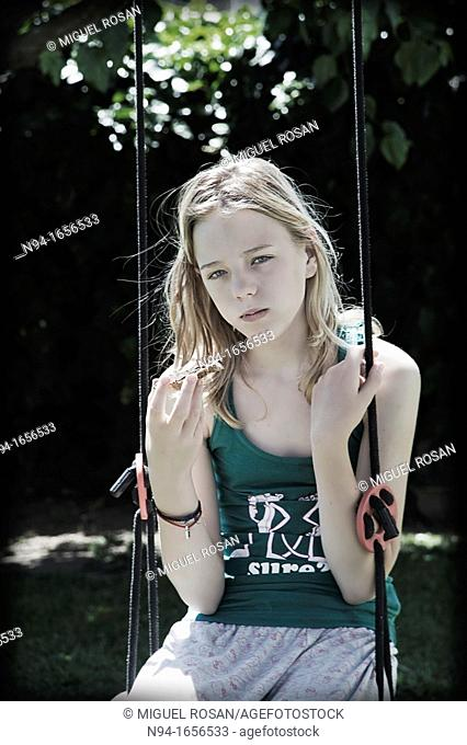 Blonde teen girl sitting on the swing with a snack
