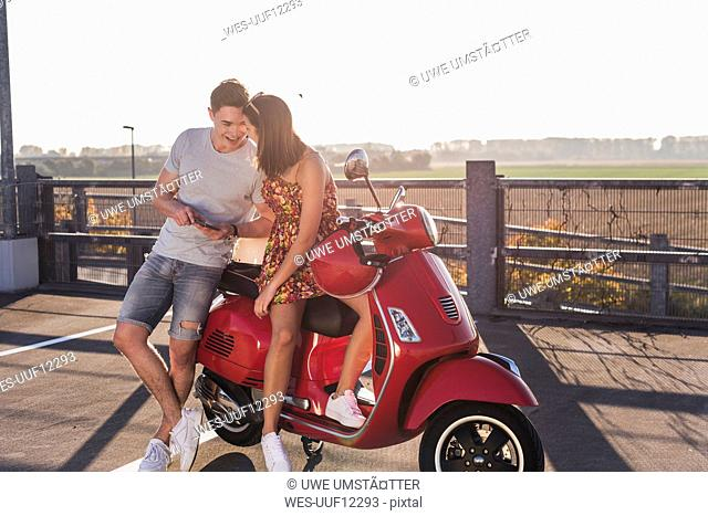 Happy young couple on parking level with motor scooter and cell phone