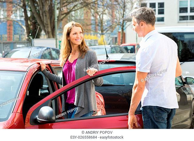 Happy Mature Couple Standing By New Car Door