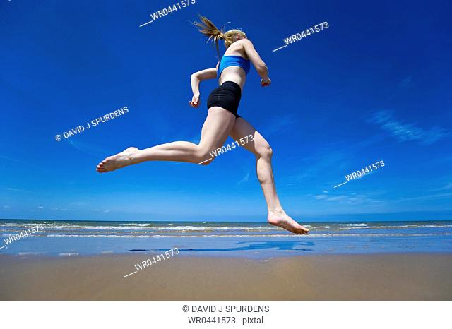 An athletic runner jogging along a sandy beach at the oceans edge
