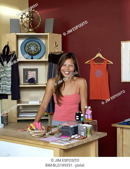 Pacific Islander woman standing at shop counter