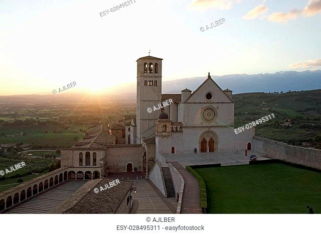 Basilica of San Francesco d'Assisi at sunset, Assisi, Umbria, Italy. The Basilica, which was begun in 1228, is built into the side of a hill and comprise two...