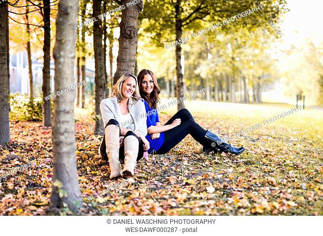 Two female friends leaning on tree trunk