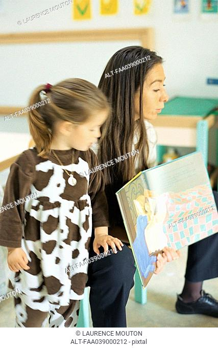Teacher reading book aloud, child standing nearby
