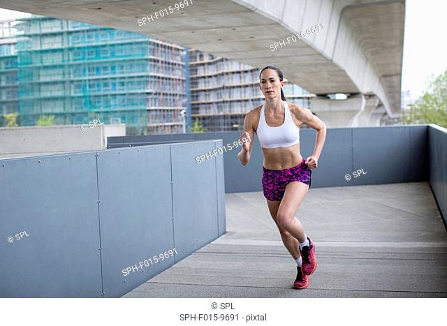 MODEL RELEASED. Young woman running in urban scene