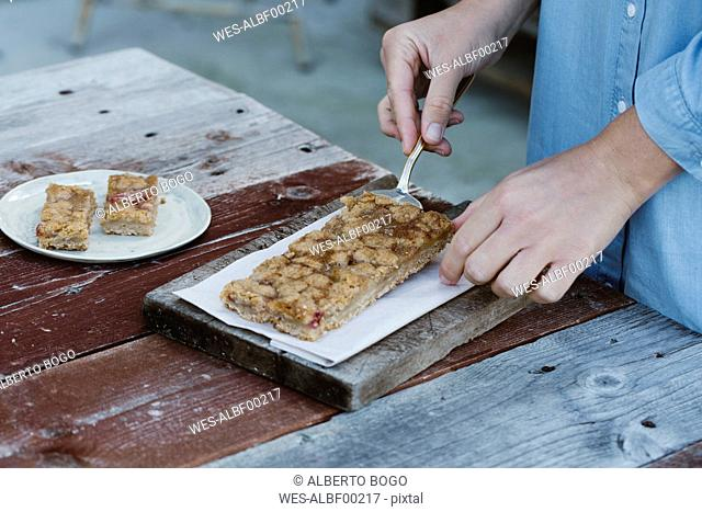 Italy, woman preparing breakfast table on terrace, partial view