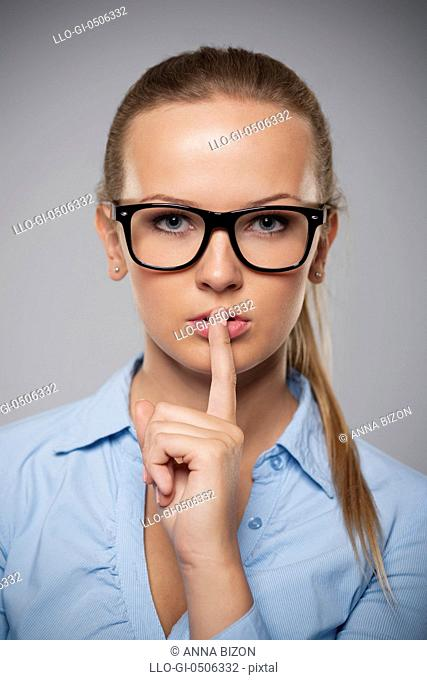 Serious woman wearing glasses showing quiet hand sign, Debica, Poland