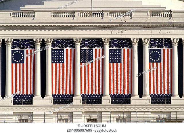 US Capitol Building with American flags draped between columns