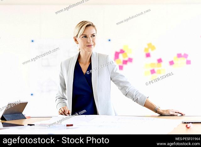 Blond businesswoman in conference room with adhesive notes at whiteboard