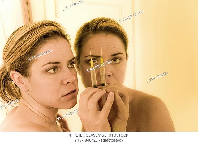 Woman holding a syringe, looking in a mirror