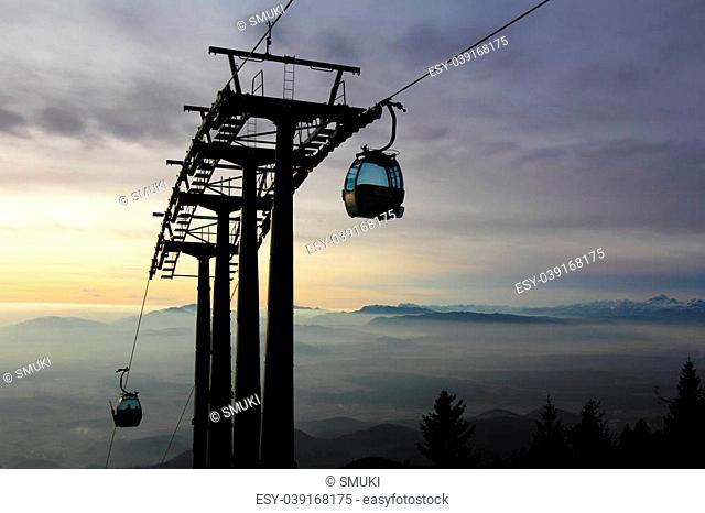 Cablecar transports skiers to the top of the mountain and the sun goes down