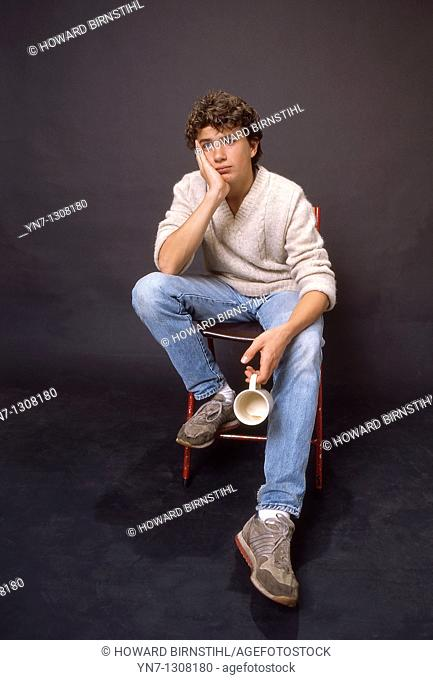 studio image of bored teenage boy sitting in chair