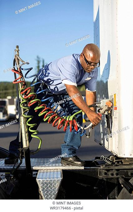 Black man truck driver attaching power cables from truck tractor to trailer at a truck stop