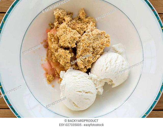 Fresh out of oven in white china bowl apple and strawberry crumble pie in traditional english dessert or pudding with vanilla ice cream scoops