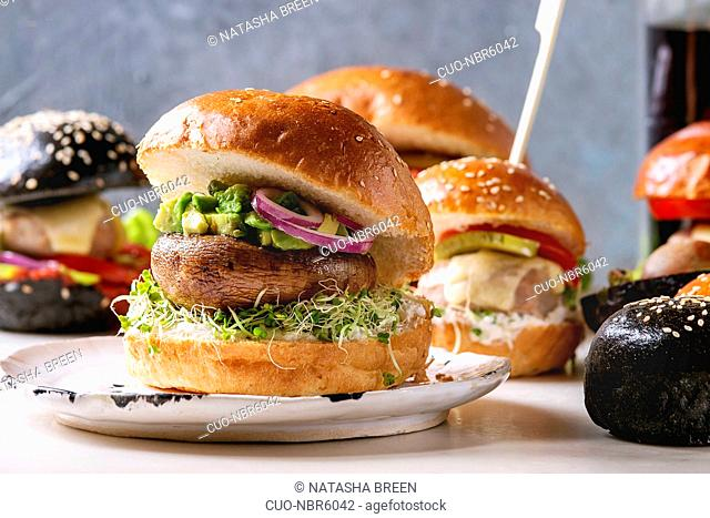Variety of homemade classic, vegan and mini burgers in wheat and black buns with beef and veal cutlets, portobello mushroom, avocado